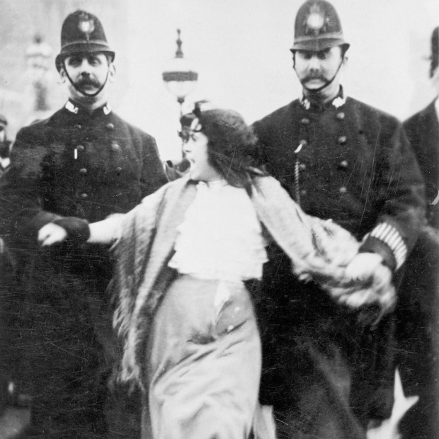 A 'Lancashire lassie' being escorted through the palace yard, Westminster Palace, London, 20th March 1907. A young woman is reluctantly escorted by two policeman who are holding her by the arms. The woman is still protesting as she is led away. The last line of the verse at the bottom says 'For Women's Rights anything we will dare; Palace Yard, take me there!' (Photo by Museum of London/Heritage Images/Getty Images)